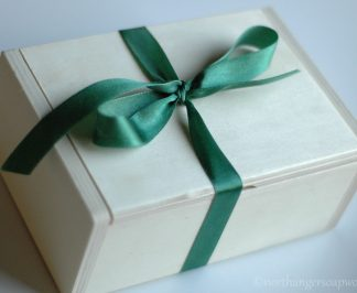 large wooden gift box with green ribbon